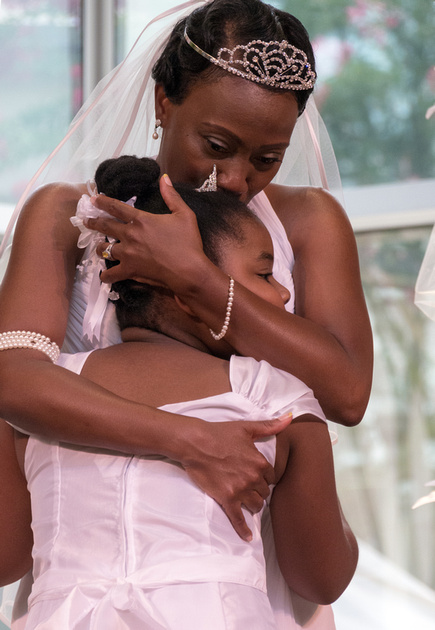 A candid moment of a bride hugging her flower girl at the wedding reception.